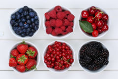 Berry fruits in bowls with strawberries, blueberries and cherrie Stock Photos
