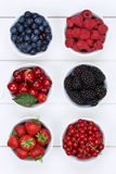 Berry fruits in bowls with strawberries, blueberries and cherrie Royalty Free Stock Image
