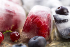 Berry fruits frozen in ice cubes Stock Photography