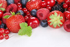 Berry fruits on wooden board with strawberries, blueberries, che Stock Photos