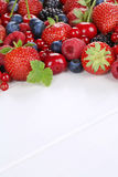 Berry fruits on wooden board with strawberries, blueberries, che Stock Photography