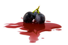 Berry grape in a wine puddle. On white background Stock Photo