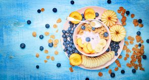 Berry greek yoghurt with frefh blueberries, banana and flakes in the pink bowl on the blue wooden table. Top view of Summer breakfast. berry greek yoghurt with royalty free stock photo