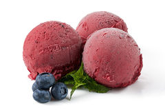 Berry ice cream balls with blueberry. And mint sprig on white background. Berry sorbet. Isolated Royalty Free Stock Image