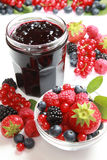 Berry jam. A glass of mixed berry jam with strawberries, bilberries, red currants, raspberries and blackberries royalty free stock photo