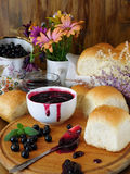 Berry jam and buns. Berry jam in a ceramic bowl, golden buns and a spoon covered with jam stock photo