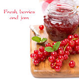 Berry jam and fresh red currants on a wooden board, isolated Stock Images