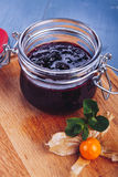 Berry jam. Glass jar of berry jam on blue background. Preserved fruits. Homemade berry jam in jar covered Stock Photography