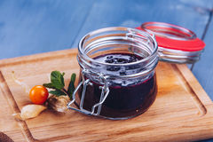 Berry jam. Glass jar of berry jam on blue background. Preserved fruits. Homemade berry jam in jar covered Royalty Free Stock Photography