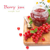 Berry jam in a glass jar and fresh red currants on board Royalty Free Stock Images
