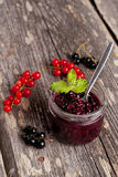 Berry jam in a glass jar and fresh red currants on wooden board,. Berry jam in a glass jar and fresh red currants on wooden board Royalty Free Stock Photography