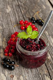 Berry jam in a glass jar and fresh red currants on wooden board. Close up Stock Photo