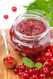 Berry jam in a glass jar and fresh red currants on wooden board Stock Photo
