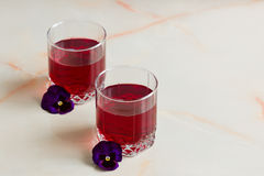 Berry juice with berries on the table in the glass jars and tuli. A refreshing summer red berry juice in a glass on a light background Stock Image
