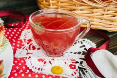 Berry juice in a transparent mug. Strawberry juice in a transparent mug on the white lace napkin stock photo