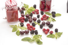Berry with leaves on the table. Fresh berry with leaves on a table and juice in a mug Stock Photography