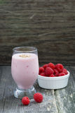 Berry milkshake and fresh raspberries on a wooden background. Vertical, closeup Stock Image