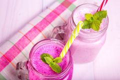 Berry milkshake or smoothie with ingredients. Healthy drink in mason jar. Berry milkshake or smoothie with ingredients and mint. Healthy drink in mason jar Stock Image