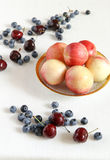 Berry mix. Peaches in a bowl, cherry and bilberry. A white cloth from flax Stock Photography