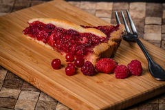 Berry pie. Slice of pie with currants, raspberries, strawberries of dough on a bamboo board Royalty Free Stock Images
