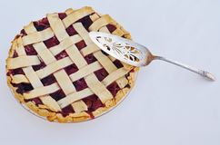 Berry pie with a spatula. A sterling silver spatula laying on a berry pie with lattice crust Royalty Free Stock Image