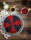 Berry pie with strawberries and blueberries. Berry tart with strawberries and blueberries on wooden table and on fabric with color dots Stock Images