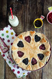 Berry pie with strawberries and blueberries. On wooden table and on fabric with color dots Royalty Free Stock Photo