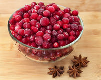 Berry on plate with anis. Frozen red berry in plate with anis nerby on wooden table royalty free stock image