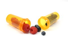 Berry Prescription. Raspberries and blueberris in pill bottles on a white background Stock Photography