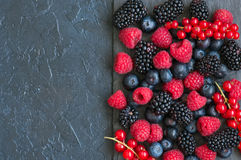 Berry raspberries red currants and blueberries on black slate bo. Ard. Gray stone background.  Top view Royalty Free Stock Photos