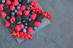 Berry raspberries red currants and blueberries on black slate bo. Ard. Gray stone background.  Top view Stock Images