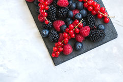 Berry raspberries red currants and blueberries on black slate bo. Ard over white stone background.  Top view Stock Image