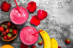 Berry smoothie with banana and rose petals. On rustic background royalty free stock images