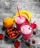 Berry smoothie with banana and rose petals. On rustic background royalty free stock photo