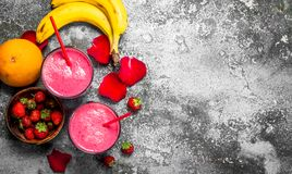 Berry smoothie with banana and rose petals. On rustic background stock photo