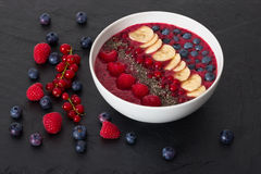 Berry smoothie bowl with chia seeds, bananas, blueberries, currant and raspberries on black slate background Stock Photo