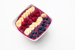 Berry smoothie bowl on white background, topped with bananas, raspberries and blueberries Royalty Free Stock Image