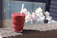Delicious red berry smoothie with some pretty flowers on the background. Berry smoothie in bright red color. Served with a white straw. The photo is taken on a Stock Images