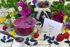 Berry smoothie in glass cup, white note with love you text, summer berries and flowers on wooden table. Morning still life with healthy breakfast. Beautiful Stock Photo
