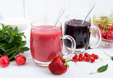Berry smoothie in of glass cups, yogurt, granola, fresh berries on white wooden background Stock Photography
