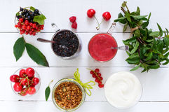 Berry smoothie in of glass cups, yogurt, granola, fresh berries on white wooden table. Top view. Proper nutrition. Royalty Free Stock Photo
