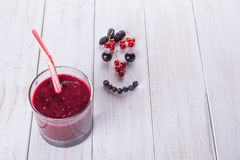Berry smoothie in a glass jar with a straw, over vintage wood table with fresh mulberry berries, blackberries and currants. Smile. From berries stock photo