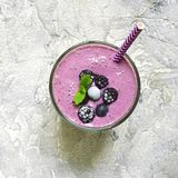 Berry smoothie in a glass with paper straw.Top view,square image. Berry smoothie in a glass with paper straw on a grey slate,stone or concrete background.Top Stock Image