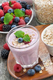 Berry smoothie with oatmeal in a glass on wooden table, vertical Stock Images