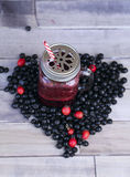 Berry smoothie. On a old wooden background. Heart shape Stock Images