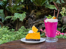 Berry smoothie and orange cake on wooden table. In garden Royalty Free Stock Photography