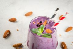 Berry smoothies with granola. Healthy food. Dietary breakfast, snack. Berry smoothies with granola, black currant, blueberries and nuts almonds, decorated with Royalty Free Stock Photos