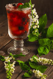 Berry soft drink with ice on a wooden background and flowers. Berry soft drink with ice on a wooden background with flowers Royalty Free Stock Image