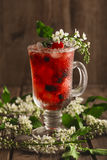 Berry soft drink with ice on a wooden background and flowers. Berry soft drink with ice on a wooden background with flowers Stock Photo
