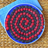 Berry spiral on the plate. Colorful striped spiral of raspberry and mulberry on blue plate Stock Image